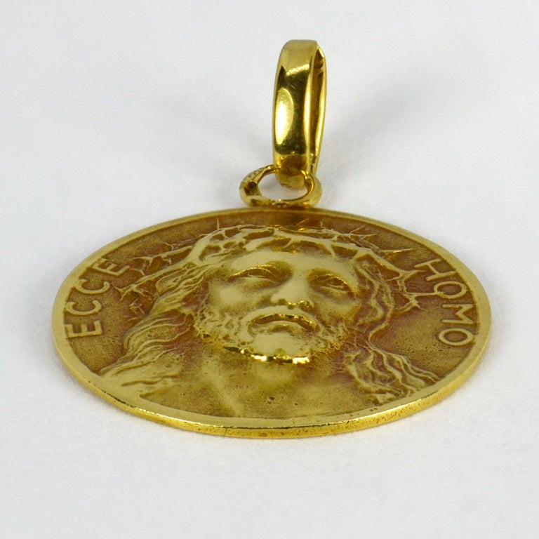 A French 18 karat (18K) yellow gold charm pendant designed as a round medal depicting Christ wearing the Crown of Thorns, with the words 'Ecce Homo' (Behold the man) - the words used by Pontius Pilate to present Jesus to the crowd before his