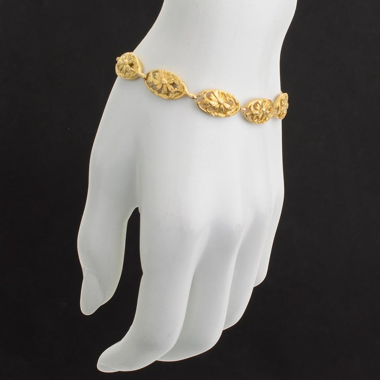 Oval-shaped link bracelet, with openwork floral motifs, in 18k yellow gold. Gold cable link safety chain. 7.5