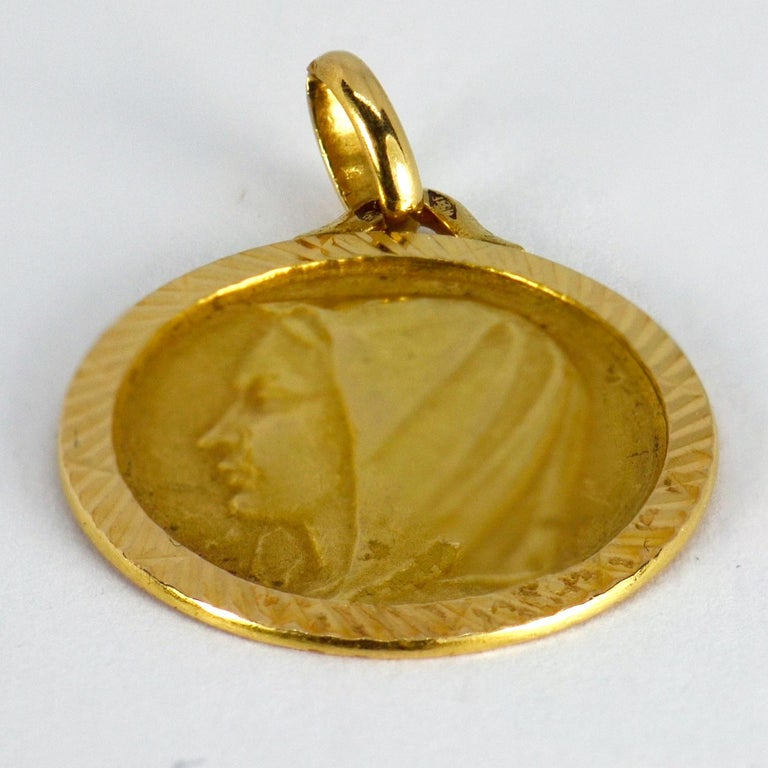 A French 18 karat (18K) yellow gold charm pendant designed as a medal depicting the Virgin Mary. Engraved to the reverse 'Martine 27-3-57'. Stamped with the French eagle's head for 18 karat gold and an unknown maker's mark.  Dimensions: 2.5 x 2.1 x