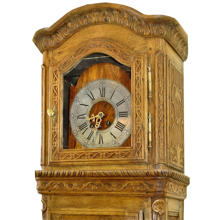An exceptional country French 18th century grandfather clock in oak. The case has fabulous detailed carvings of scrolls, flowers and acanthus leaves. The clock has all original hardware including lock and key.