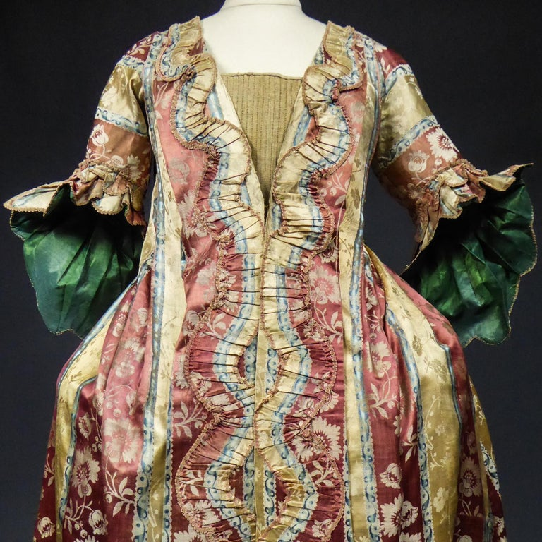 Circa 1740/1760 France  Rare Louis XV robe volante (or flying dress) or interior coat between 1740 and 1760. Shaded satin damask with wide stripes adorned with floral garlands in brick, sky-blue, straw-yellow and cream tones. Typical pyramidal cut