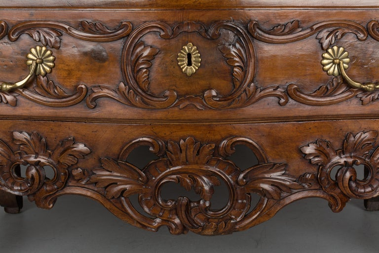 A fine 18th century Louis XV period commode from the town of Nîmes in Provence. Made of solid walnut with serpentine front and raised panels on the sides. Pegged construction with waxed finish. Beautiful hand carved foliate decoration including an