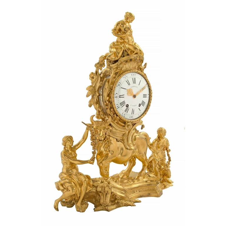 A magnificent and very high quality French 18th century Louis XV period ormolu clock. At the base is a scene of two maidens draped in flowing garments holding finely detailed floral garlands, centered by an impressive bull. Above is the enamel dial