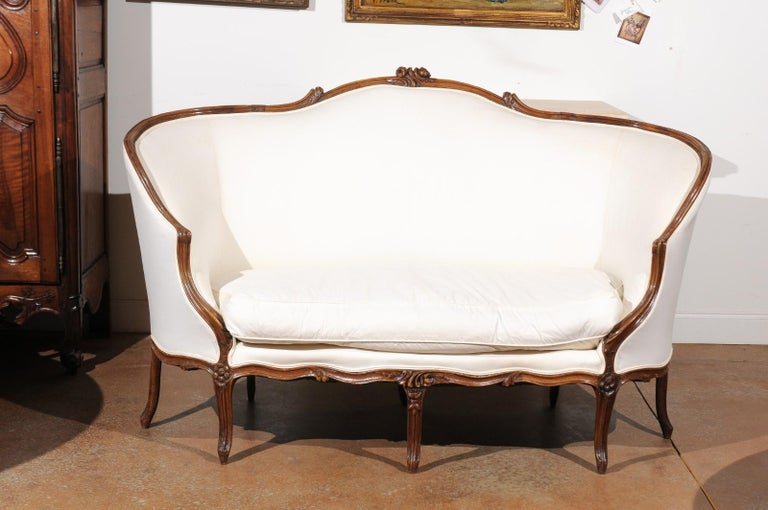 A French 18th century Louis XV period walnut wraparound sofa from Lyon, with upholstery and cabriole legs. Born in the Rhône Valley during the 18th century, this exquisite canapé features a wraparound back, accented on its upper rail with two