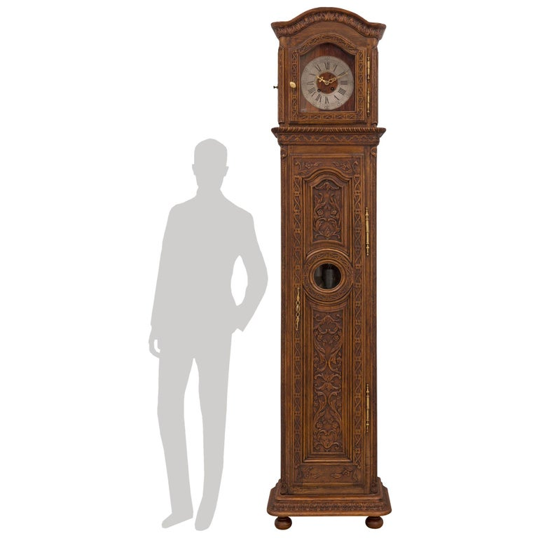 A most elegant French 18th century Louis XVI period oak grandfather clock. The clock is raised by fine bun feet below a mottled finally carved foliate band. The case displays one door with elegant ormolu hinges, a pianist keyhole escutcheon,