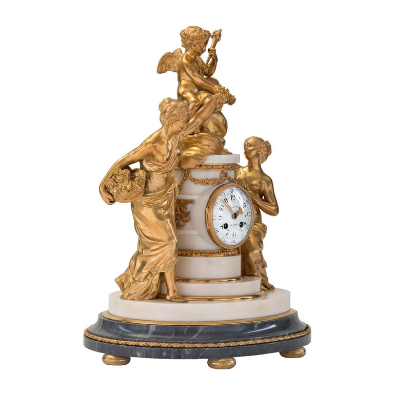 An extremely elegant and very high quality French 18th century Louis XVI period ormolu, Bleu Turquin and white Carrara marble clock signed by Jean-Baptiste Dutertre. The clock is raised by six ormolu bun feet below the oval-shaped mottled Bleu
