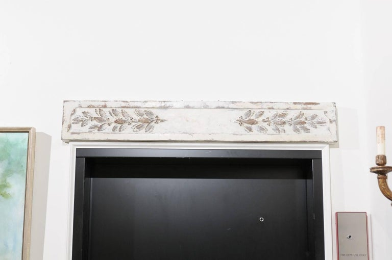 A French 18th century carved and painted wood panel with foliage motifs from Arles, South of France. Born in the Provençale region of France, this carved horizontal panel features a distressed off-white background from which delicate leaves seem to