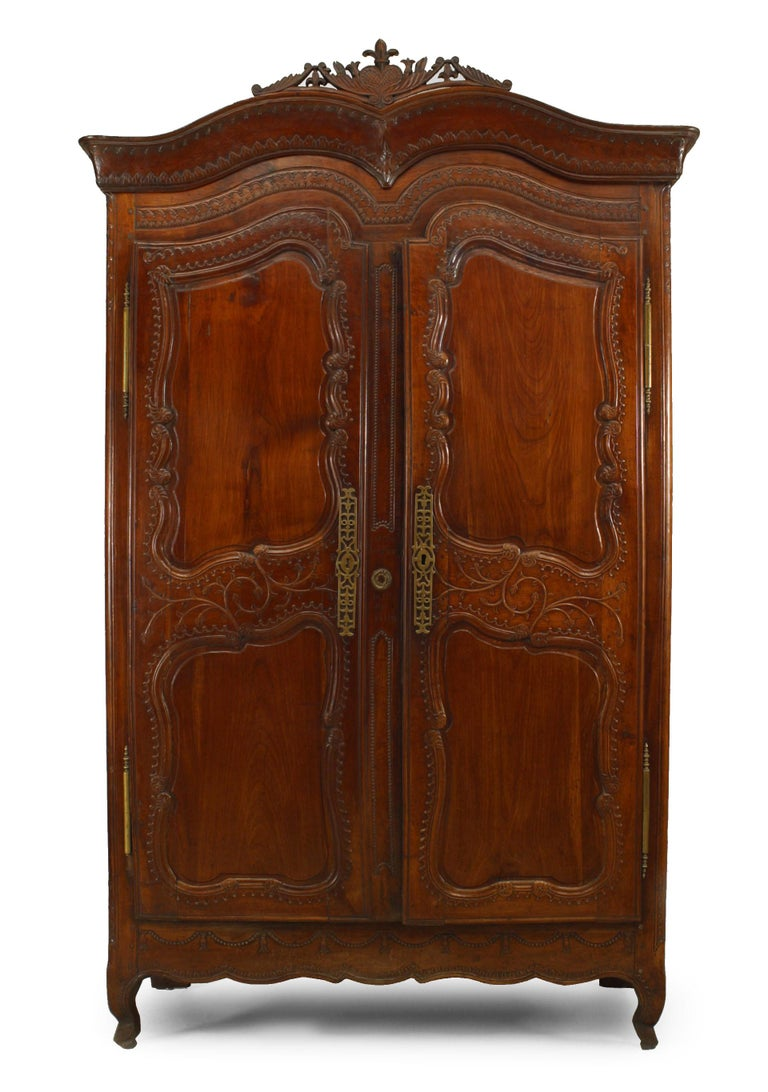 French Provincial 18th century walnut carved armoire with double scroll top and 2 doors with carved border.