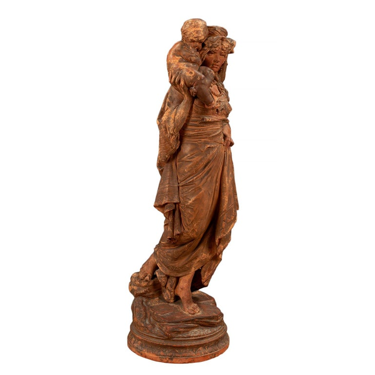 A wonderful French 18th century terracotta signed statue of mother and child. The statue is raised on a circular terrain designed base. The woman is barefoot donned in a traditional gown with a pearl styled necklace and head dress. The woman is
