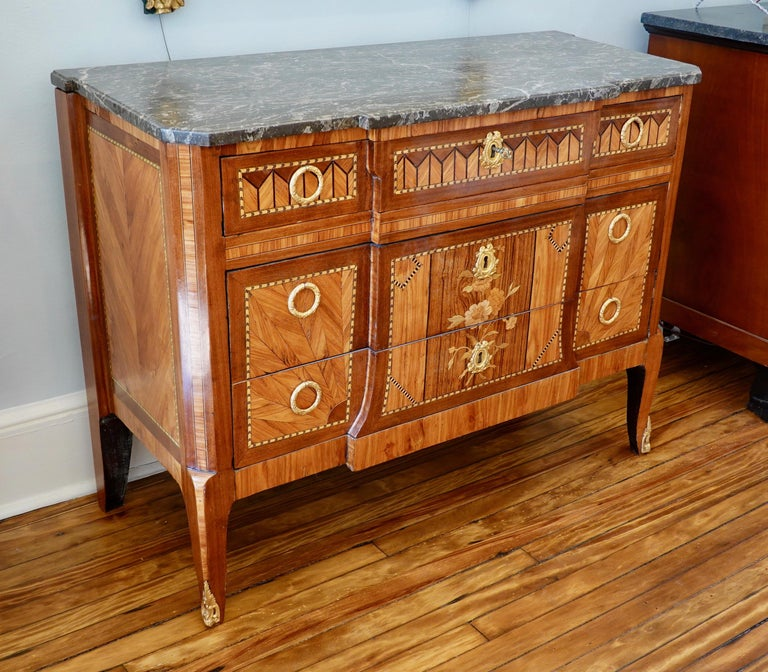 French Louis XV-XVI transitional period commode with lovely marquetry in satinwood, rosewood and tulipwood, Gris Sainte Anne marble top and three drawers. The commode features a central marquetry design of a bouquet of flowers spanning the lower two
