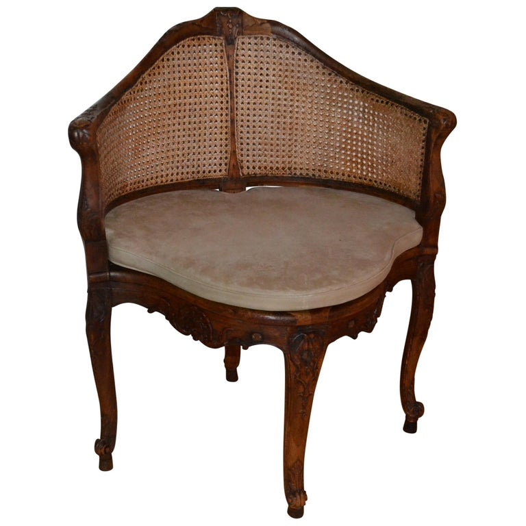 18th Century French walnut corner caned chair with a thin parchment colored leather pillow.