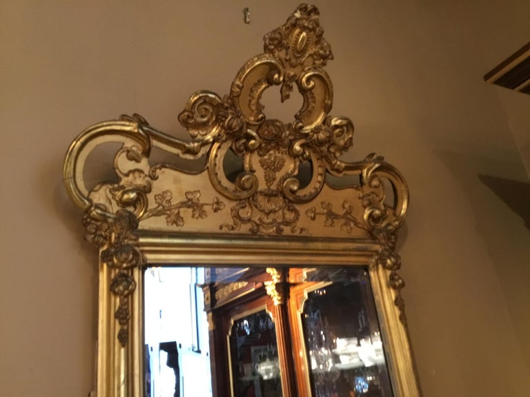 Lovely old original giltwood with antique patina. The top crest bends gently forward in design. Fruit and foliate carvings decorate this exceptional mirror.