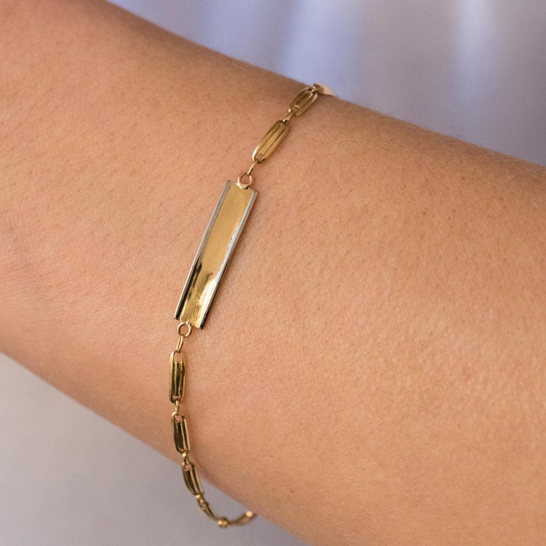 Bracelet in 18 karats yellow gold, eagle's head hallmark. Lovely little antique bracelet, it is formed of a mesh made of gold staples holding a small yellow gold plate edged with white gold. The clasp is a spring ring. Total length: 17 cm, width: