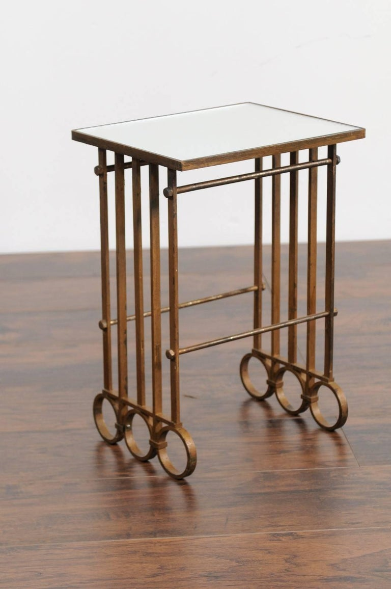 A French gilt iron drink table from the early 20th century with lath and ring sides and new mirrored top. This French iron drink table features a rectangular top supporting a new custom-made mirror, raised on an unusual base, made of lateral laths