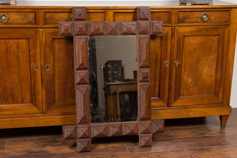 A French Tramp Art hand carved mirror from the early 20th century with raised pyramidal motifs and intersecting corners. Born in France during the early years of the 20th century, this French mirror was hand carved in the manner typical of the Tramp
