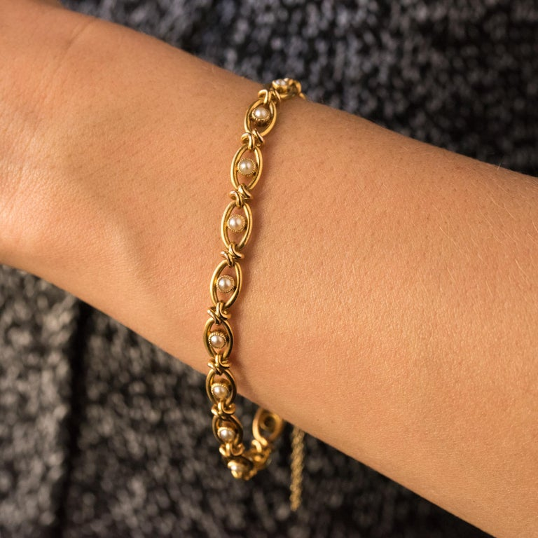 Bracelet in 18 karats yellow gold, eagle's head hallmark. This charming antique bracelet is made of openwork shuttle mesh set with natural pearls, held together and articulated by a small knot. The clasp is ratchet with safety chain. Length: 19 cm,