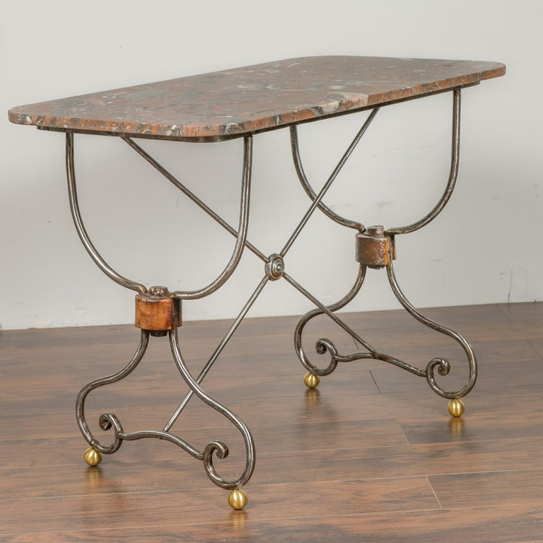 A French steel and brass console table from the early 20th century, with variegated marble top and scrolling feet. We have a twin table available, see item LU836719327322 should you need a pair. They are priced and sold individually. Born in France