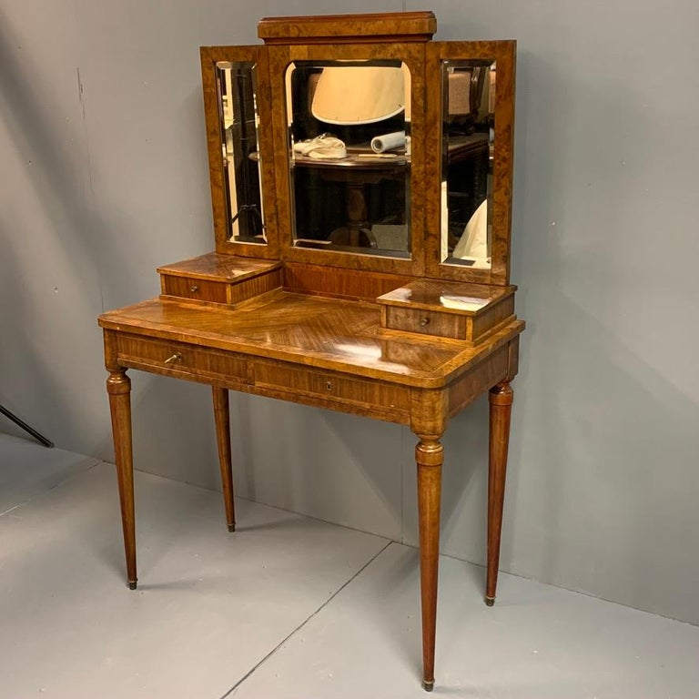 Good decorative and practical size French neoclassical mahogany and burr walnut dressing table with triple bevelled mirrors and good storage, circa 1920.