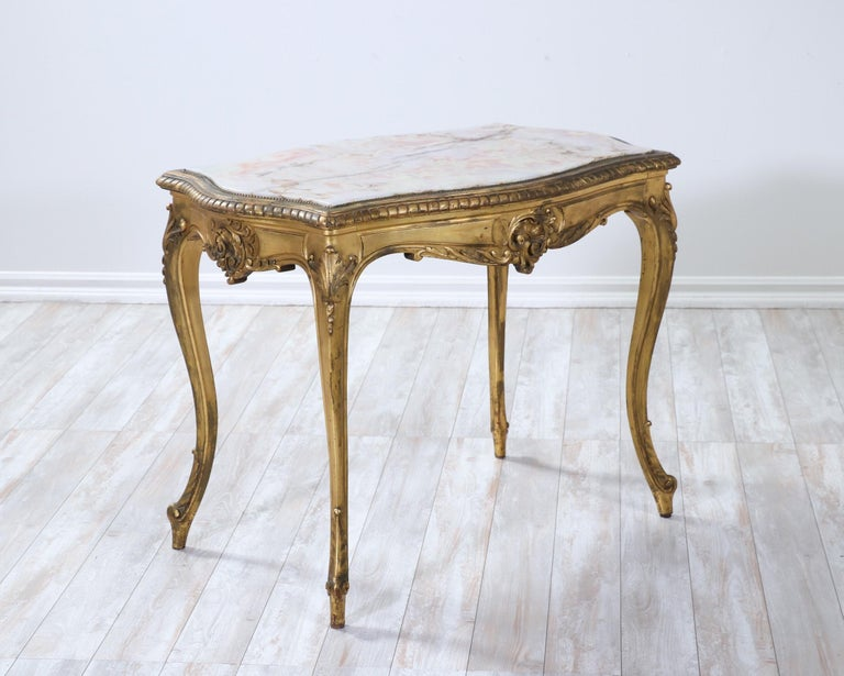 """Beautiful, French 1920s giltwood and onyx-marble salon table in the Louis XV style.  Delicate carvings are featured in this """"very French"""" salon or side table including a rocaille-themed apron and cabriole legs. The naturally aged gilt finish"""