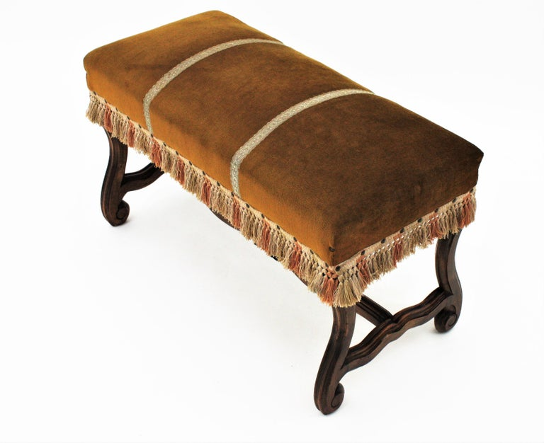 An early 20th century backless Louis XIV style bench or stool raised on four Os de Mouton hand carved walnut wood legs with stretcher. France, circa 1930s. This stylish banquette has scrolled accents on the legs. This bench is in exquisite fully