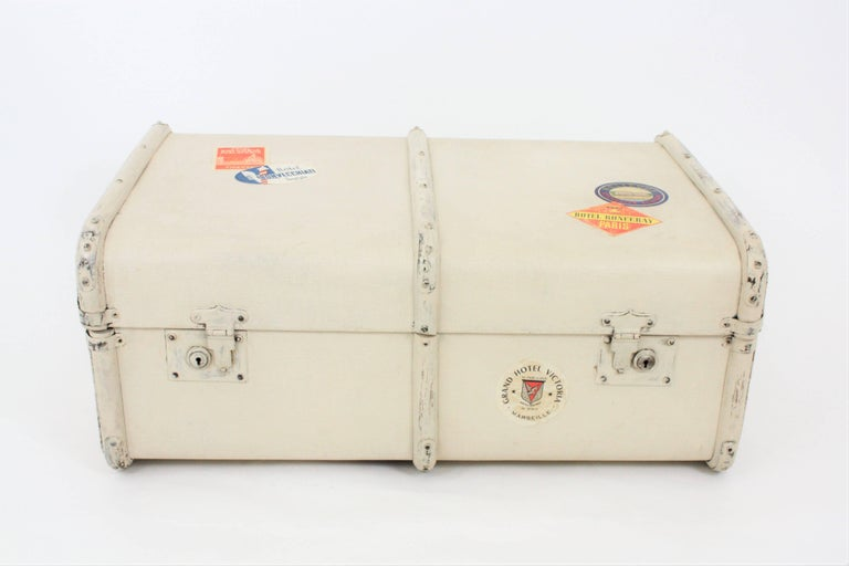 A vintage wood and textile canvas vintage trunk manufactured at the Art Deco period.  It is patinated in ivory color with hotel labels, wooden bars, metal protections and leather handles. Lovely to be used as an storage piece or as a coffee table or