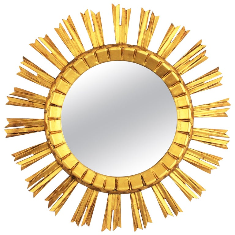Eye-catching Baroque style sunburst / starburst wall mirror. France, 1930s.  The mirror is made in carved wood, covered with gesso and has gilt finish. Lovely to be placed alone or creating a wall composition with other sunburst mirrors. Overall