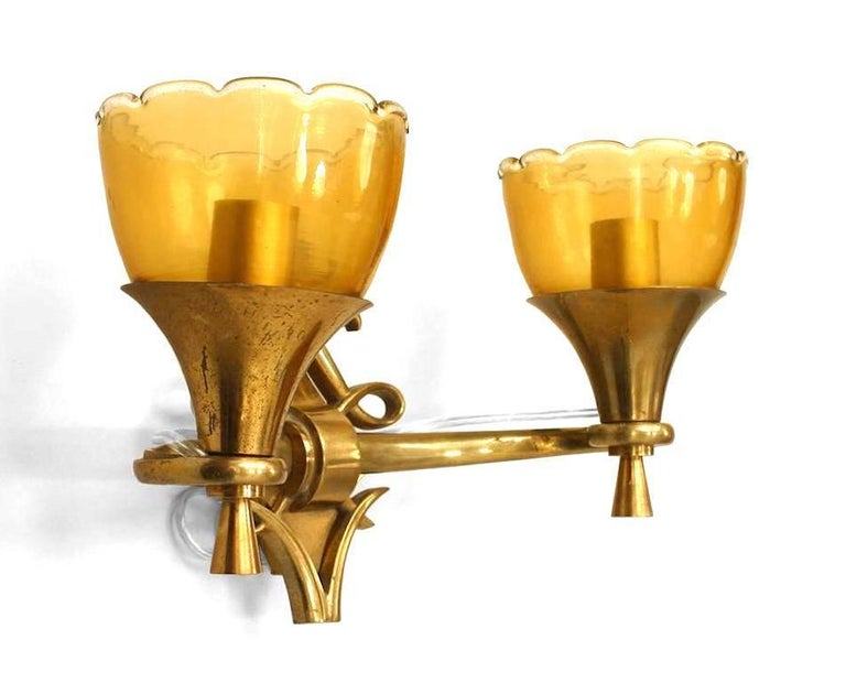 French 1940s brass two-arm wall sconces with diamond form and scrolling backplate and amber glass scalloped top shade.
