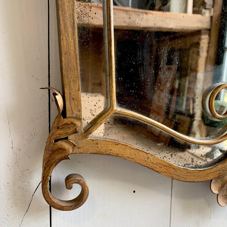 A French 1940s gilt metal mirror, with decorative scrolls, shield form.