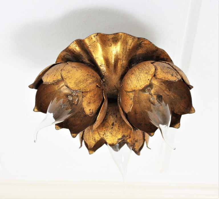 A beautiful hand-hammered Hollywood Regency gold leaf gilt iron light fixture with 3 flower bulb holders. France, 1940s. It can be used as a flush mount or as a wall light and it also could work as a table lamp. It can add a pinch of glam in a