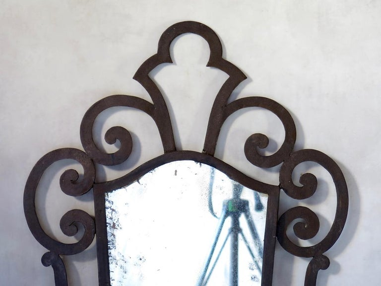 Baroque 1940s style wrought iron mirror. The looking glass has a peeling back. Wooden back.