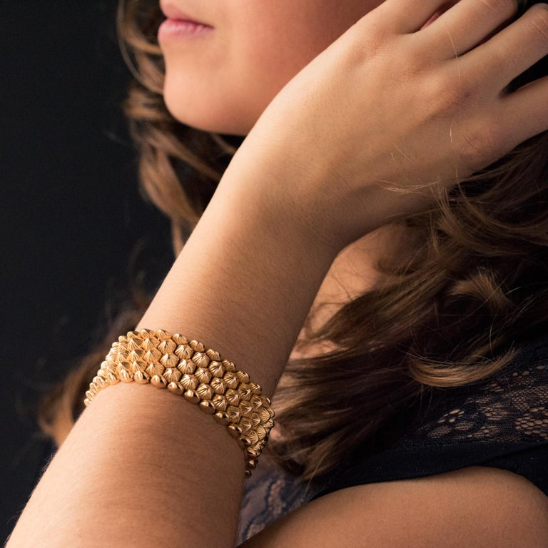Bracelet in 18 karat yellow gold, eagle's head and rhinoceros hallmark. Flexible, this retro gold bracelet is made of chiselled honeycomb patterns. The fastening system is ratchet with two safety 8. Length: 19 cm, width: 2.5 cm, thickness: 4.9