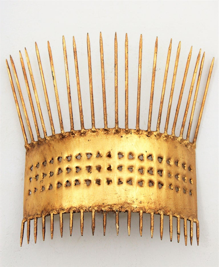 Unusual hand-hammered gilt iron sunburst wall sconce with gold leaf finish and Art Deco accents in transition to Brutalist style.  France, 1950s. A highly decorative piece with iron nails at the top and at the bottom. The central part is adorned by