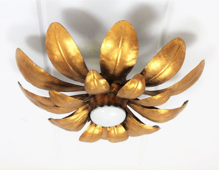 Monumental hand-hammered iron double layered leafed sunburst flush mount or light fixture with gold leaf finishing and a central light. The shape of its leaves is full of movement and highlights its beauty.  France, 1950  Avaliable a huge