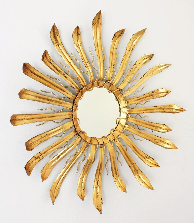 A French, 1960s hand-hammered gilt iron sunburst mirror with a layer of large leafed beams a layer of small beams and a curved pattern surrounding de glass. France, 1950s-1960s Available a huge collection of mirrors in this manner and in other