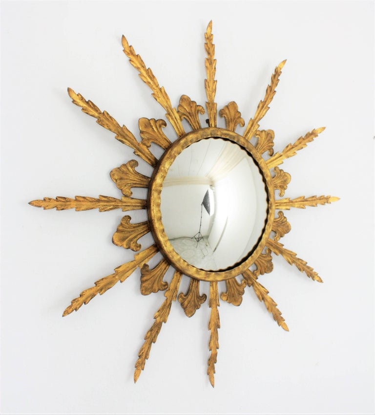 A lovely gilt iron Hollywood Regency sunburst mirror with leafed frame, gold leaf finish and convex glass. This piece has a beautiful original vintage patina. Interesting to place it alone but also gorgeous placed with other sunburst mirrors to