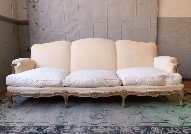 A large French sofa in the Louis VX style, most likely from the 1950s. The sofa has 3 loose seat cushions and a tight back, and is ready to be upholstered. Sold as is.