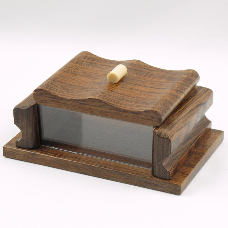Elegant hand carved modernist decorative lidded box. Rectangular shape with solid rosewood and crystal clear Lucite on sides, ornate with off-white Galalith stick handle. Original sticker underside read: 'Bois des Iles Garanti' (French for 'Exotic