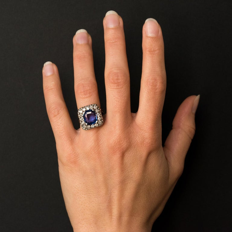 Ring in platinum, dog's head hallmark. Rectangular, this sublime retro ring is set with 4 claws of a cushion- cut blue sapphire surrounded by 16 diamonds, all lined with a twist. The ring consists of 4 threads that meet at the base. Sapphire weight: