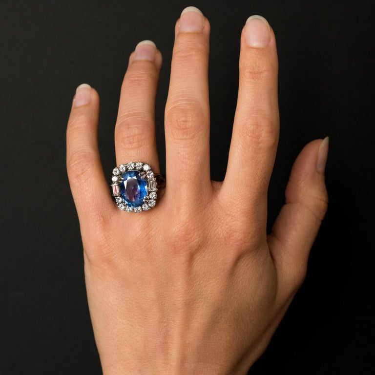 Ring in platinum, dog's head hallmark. Important rectangular shape antique ring, it is set with 4 double claws, of an oval blue sapphire surrounded by 2 x 7 brilliant- cut diamonds and shouldered with 2 baguette diamonds. The ring consists of wires