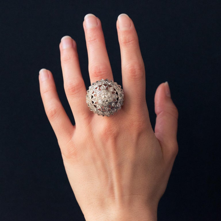Ring in 18 karat white gold, owl hallmark. Superb ball ring, it is composed in its center of an openwork sun motif set with diamonds. The mounting is surrounded by a row of diamonds. The entire border is serrated and punctually set with diamonds.