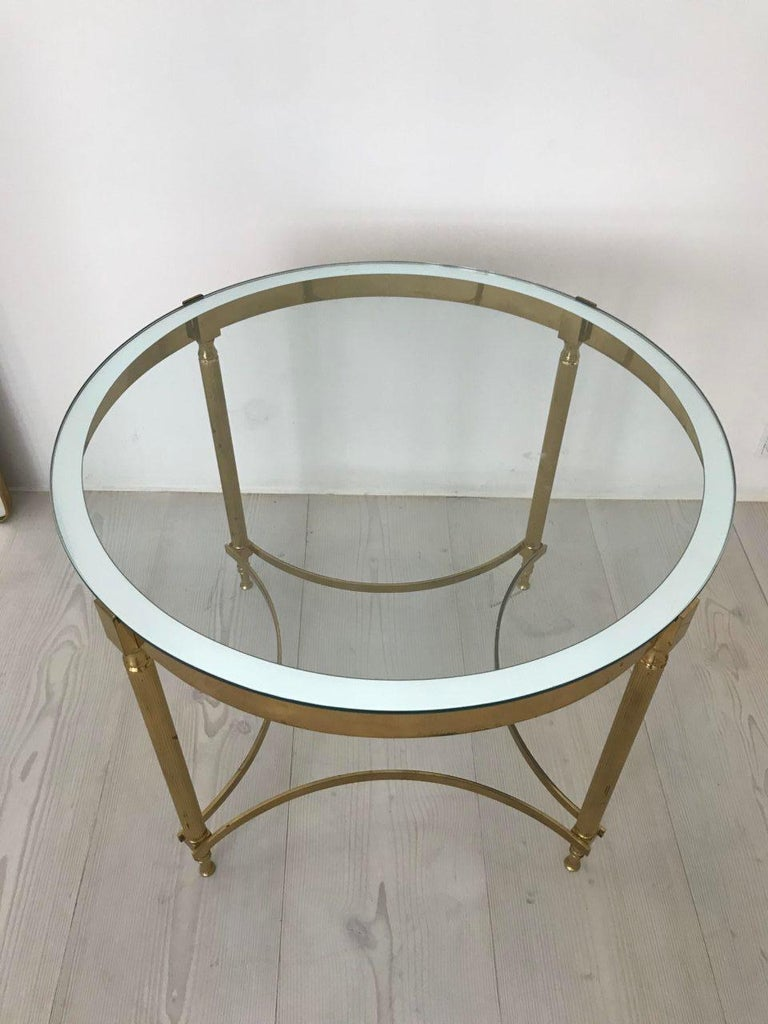 Sophisticated and beautiful tall circular coffee / lamp table. Made in brass, and from 1960s France. Elegantly made with a sleek brass frame holding a solid quality glass top with a mirrored edge giving a lovely finish, and standing on fluted