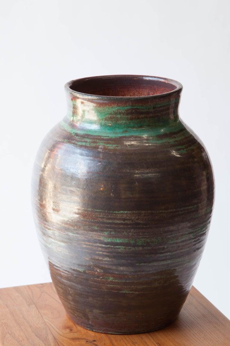 A ceramic jar with a glaze reminiscent of verdigris or raku firing. A soft sheen. Accolay, France. 1960s. Signed