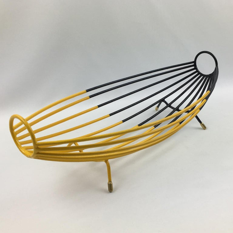 Stunning 1960s modernist metal fruit bowl or basket or centerpiece. Black and yellow paint patina with polished brass feet. Elongated hammock shape with thin metal rods. Bi-color geometric paint design. No visible marking. Measurements: 15 in. wide