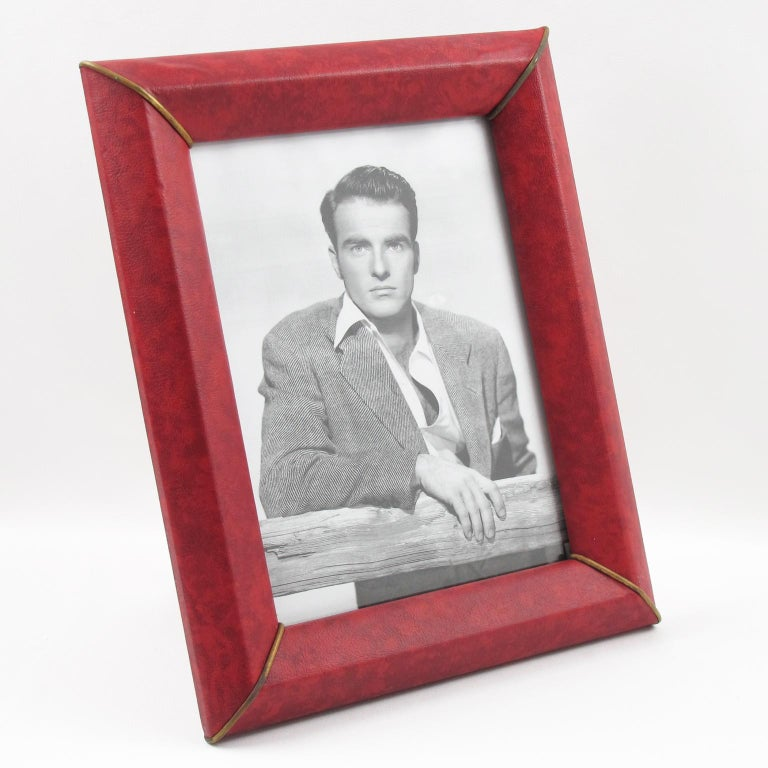 1960s modernist French picture photo frame. Decorative imitation leather (vinyl) with textured pattern in red and black marble color and brass corner accents. Back and easel in decorative paper. The frame can be placed in portrait or in landscape
