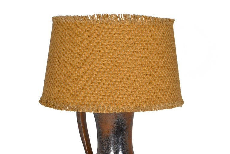 Signed Vallauris on the base this unusual big jug shaped vase is mounted as a table lamp with a straw-colored raffia shade. The vase has a wonderful grey brown patina.