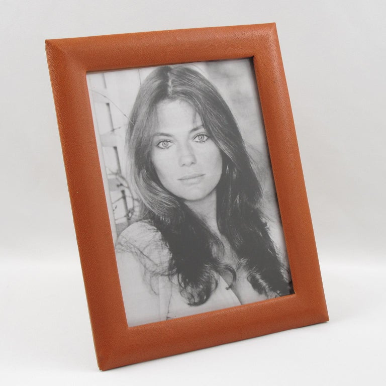 Elegant 1970s modernist French picture photo frame. Natural cognac leather with pattern. Easel and back in decorative cognac paper and glass protection on front. Frame can be placed in portrait or in landscape position. 
