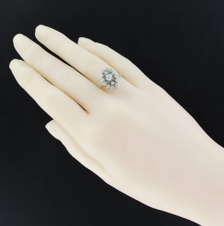 Ring in 18 karats white gold, eagle's head hallmark Marquise shape ring, this authentic vintage ring is set with claws of a modern brilliant cut diamond in an entourage of 14 diamonds also set with claws. The basket is enhanced and made of gold