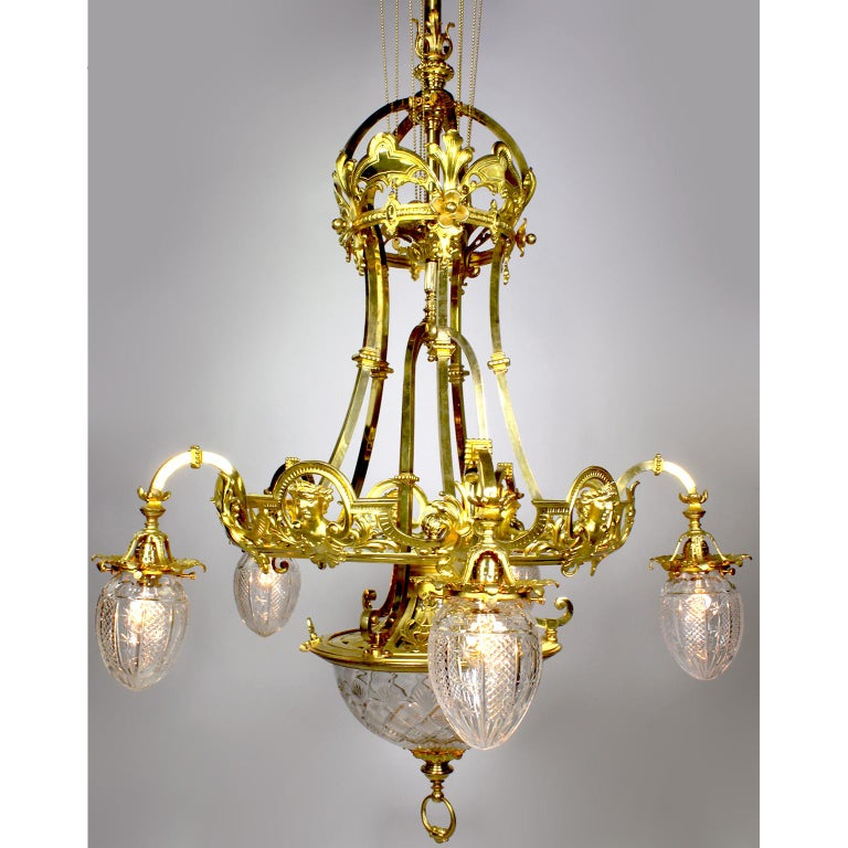 A fine and large French 19th-20th century Belle Époque gilt-bronze and cut-glass six-light figural chandelier. The elongated gilt-bronze body with a pierced apron and silvered lining with a beaded brass chain suspension around pulleys, decorated