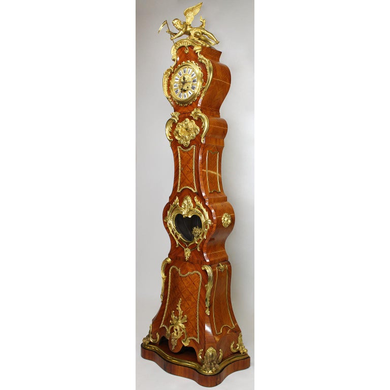 A fine French 19th-20th century Régence style gilt bronze mounted tulipwood parquetry regulator longcase clock, after the 18th century model by Julien Le Roy (French, 1686-1759) and Charles Cressent (French, 1685-1768). The asymmetrical