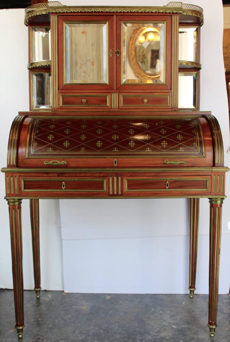 Interesting Louis XVI style mahogany cylinder desk with a white marble top having a brass gallery rail and under which a cabinet with two mirrored glass doors, four quarter round mirrored shelves and two short drawers. All glasses are beveled.